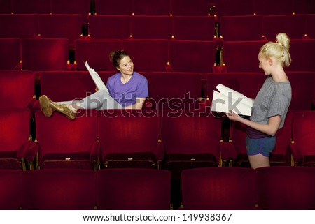 Two young women sitting in theatre stall with scripts - stock photo