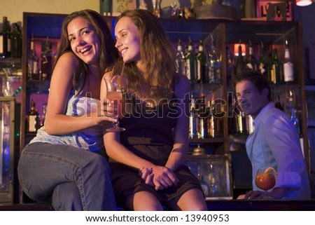 Two young women sitting on a bar counter, enjoying cocktails - stock photo