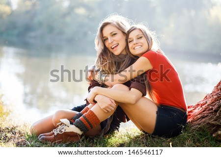 two young women sitting on grass having good time - stock photo