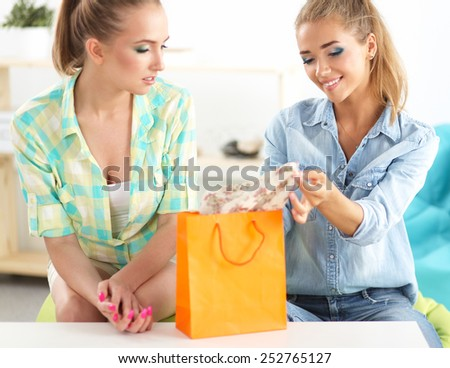 Two young women sitting with shopping bag at home . - stock photo