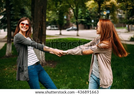 Two young women smiling and dancing in the park.  Best friends - stock photo