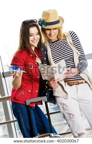 Two young women stand with a suitcase at the railway station or the airport. Look at the card and passport. Europeans. Gathered in a guided tour. - stock photo