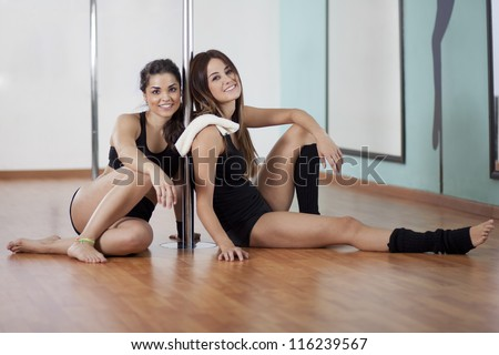 Two young women taking a break from a pole fitness class - stock photo