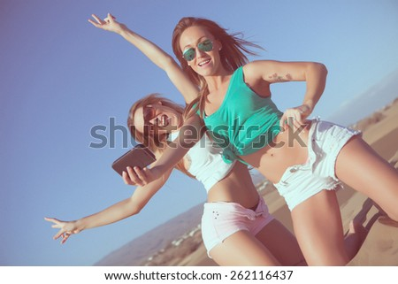 two young women taking a selfie in the beach with vintage edition - stock photo