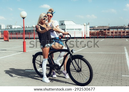 two young women taking selfie with mobile phone. Swag teen girls on black bike. Outdoor lifestyle portrait - stock photo