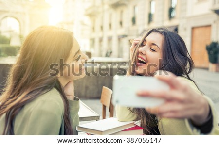 Two young women taking selfie with smart phone in the city center. Happiness concept about people and technology - stock photo