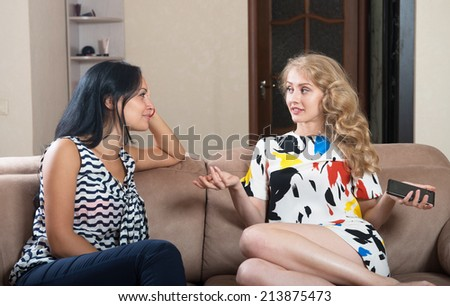 Two young women talking - stock photo