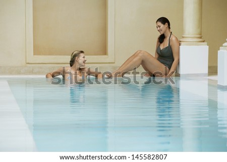 Two young women talking at edge of swimming pool - stock photo