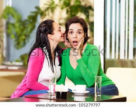 Two young women telling secrets in a cafe - stock photo