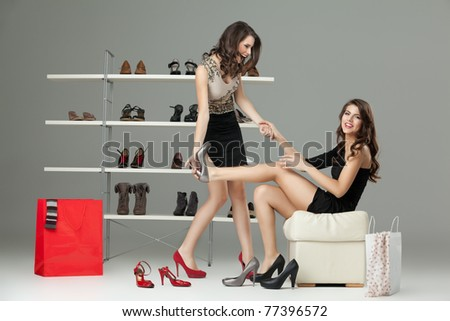 two young women trying on high heels - stock photo