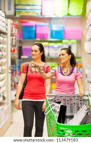 two young women walking in supermarket with trolley - stock photo
