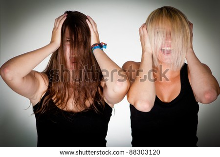 Two young women with hair over their head - stock photo