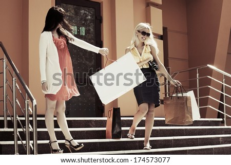 Two young women with shopping bags on the steps - stock photo