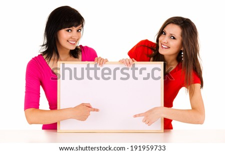 two young women with whiteboard, white background - stock photo