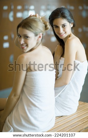 Two young women wrapped in towels, sitting on bench in locker room - stock photo