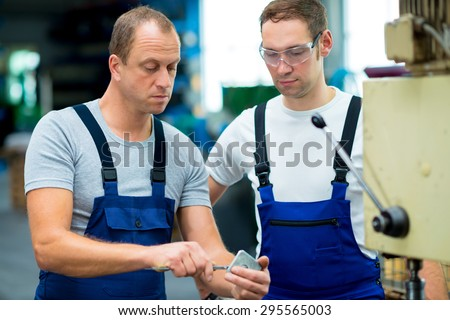 two young worker in factory on the machine - stock photo