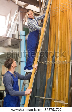 Two young workers choosing PVC window profile at stand - stock photo