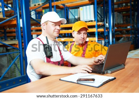 two young workers man in uniform in front of warehouse rack arrangement stillages using notebook laptop computer - stock photo