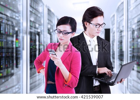 Two young workers working with a laptop computer and mobile phone in the data center room - stock photo