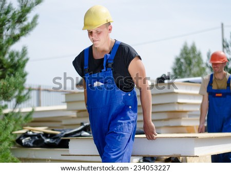 Two young workmen carrying an insulated wooden wall panel on a building site as they move it from the stacked building supplies - stock photo