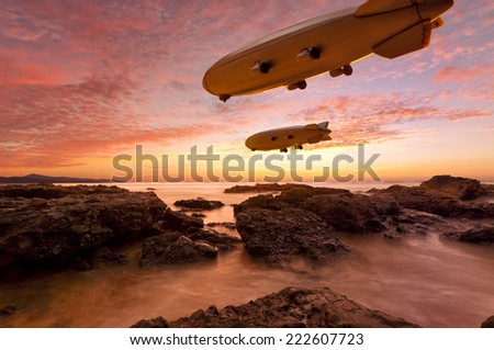 Two Zeppelins gliding above a rocky coast in vibrant sunset - stock photo