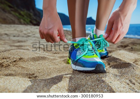 Tying laces on sneakers shoes to jog on the beach. Young woman runner tying shoelaces. - stock photo