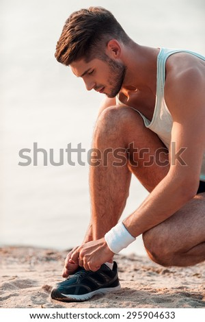 Tying shoelaces for good running. Close-up of man tying shoelaces on sports shoe while sitting on the beach - stock photo