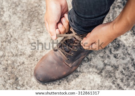 Tying Shoes on cement floor - stock photo
