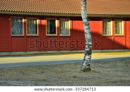 Tyipical home in norway with red walls, and breeze on yard, In Scandinavia - stock photo