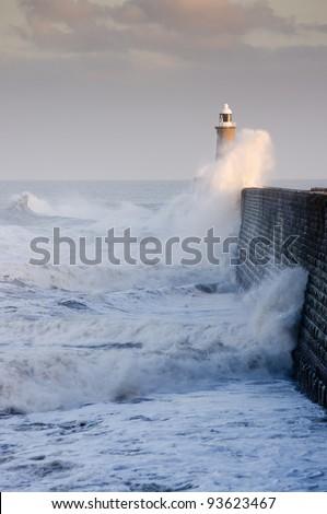 Tynemouth north pier and crashing waves / Waves crashing against Tynemouths pier and lighthouse - stock photo