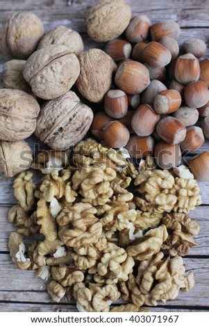Types of nuts. Walnuts in closeup. Walnut kernels and whole walnuts on rustic old wooden table. Hazelnut on wooden  background - stock photo
