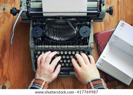 typewriter retro hand on wooden table - stock photo
