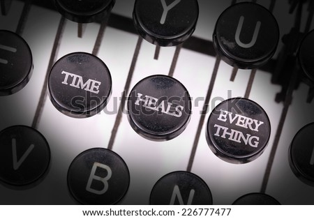 Typewriter with special buttons, time heals everything - stock photo
