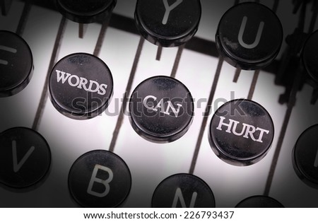 Typewriter with special buttons, words can hurt - stock photo