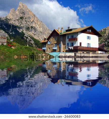 Typical alpine house on the bank mountain lake - Dolomiti - Italy - stock photo