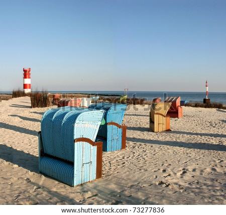 Typical beach chairs in front of the beautiful and small lighthouse of Helgoland Duene, island in the german North Sea - stock photo