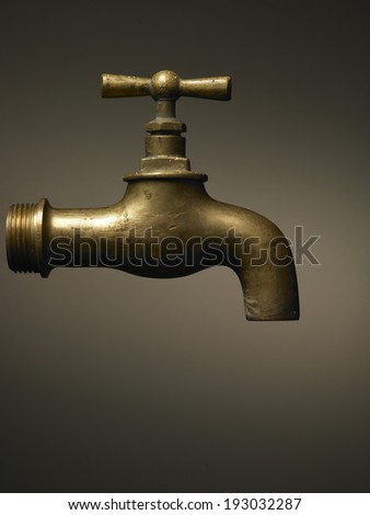 typical brass faucet on brown background gradient  - stock photo