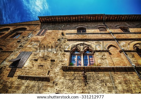 typical building in San Gimignano under a blue sky with clouds, Italy - stock photo
