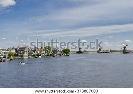 Typical buildings and windmills, to channel water passes a boat, at Zaanse Schans, Amsterdam, Holland - stock photo