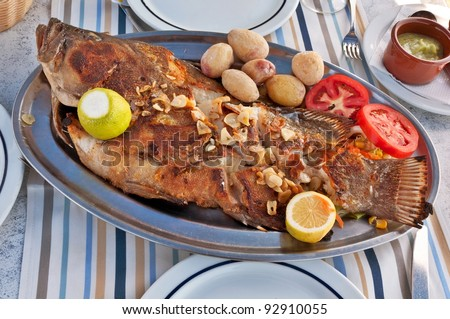 Typical Canarian Roasted sea fish on plate with tomatoes, potatoes, lemon and spices - stock photo