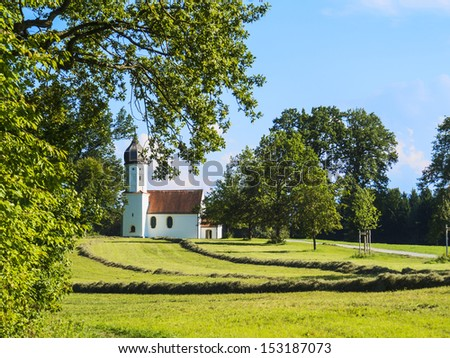 Typical chapel on green meadow with trees and mountains in Bavarian alps - stock photo