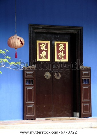 Typical Chinese mansion with wooden door & gate, lanterns & chinese quotes in pair - stock photo