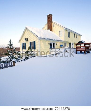 Typical colonial style house in deep snow and ice - stock photo