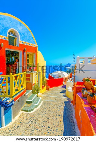 Typical colorful narrow street in Oia the most beautiful village of Santorini island in Greece - stock photo
