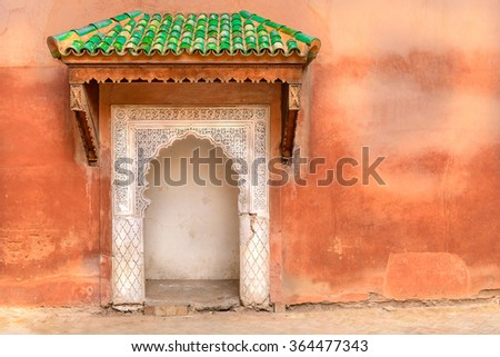 Typical decorated Moroccan door with green roof and ethnic handmade decoration.   Rough wall with small multicolor port entrance in Arabic style decoration. Concept of  freedom to travel around world. - stock photo