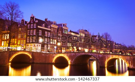 Typical Dutch houses around canals in Amsterdam, the Netherlands. Photographed in the evening. - stock photo
