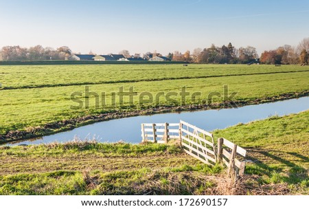 Typical Dutch landscape with a wooden fence and a ditch in the foreground and green grassland and the edge of a small village in the background. - stock photo