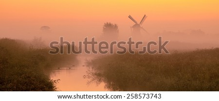 Typical dutch landscape with Characteristic historic windmill on a foggy september morning in the Netherlands - stock photo