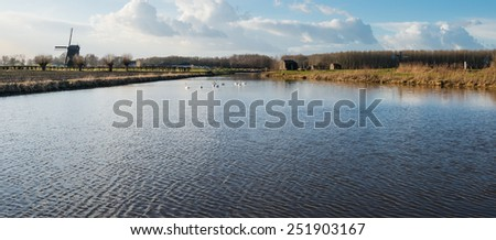 Typical Dutch polder landscape on a sunny day in wintertime with an historic windmill and a concrete bunker in the background. - stock photo
