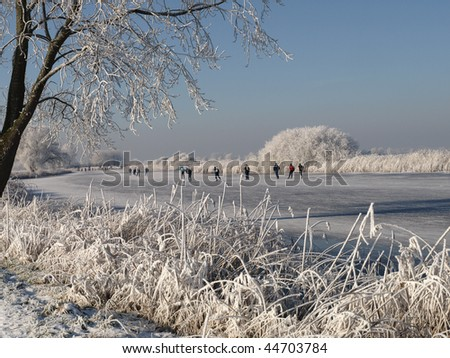 typical dutch scenery, ice skating on a frozen river in the countyside of the netherlands - stock photo